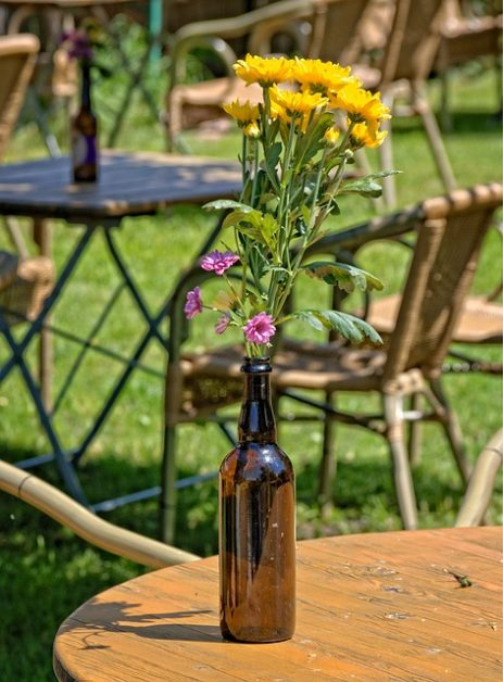 yellow flowers in a brown beer bottle