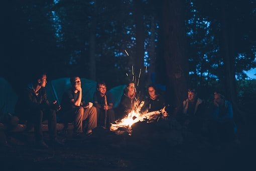 friends sitting around the campfire cooking food