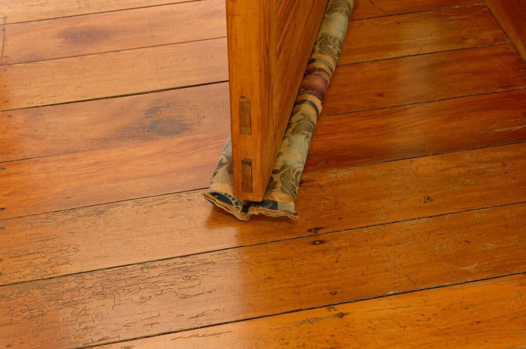 A double draft stopper made from fabric slides under a wooden door and moves with the door when it is opened